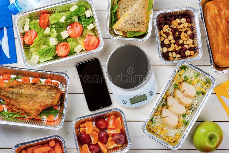 Lean fish and food scale. Smartphone and food scale, close-up. Lean fish, rice with chicken and corn, salad, baby carrots, low-calorie bread with cheese, a pie royalty free stock image