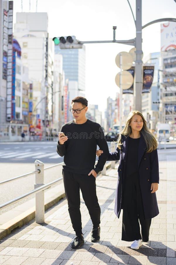 Smartphone funcionando de los pares jovenes en un camino para la información en Japón fotografía de archivo