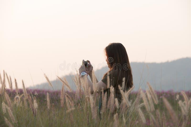 Smartphone Gebrauch der jungen Frau, der Foto im Garten macht lizenzfreies stockbild
