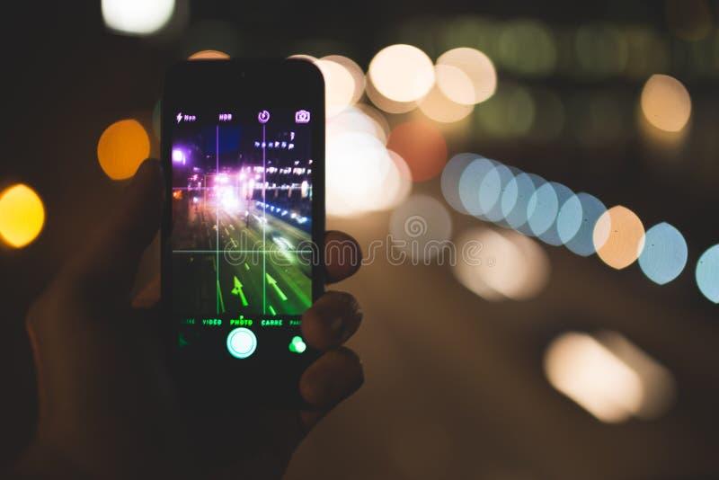 Smartphone gegen städtisches bokeh lizenzfreie stockfotos