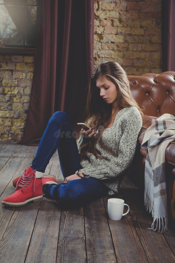 smartphone genom att använda kvinnan Koppla av tid under kallt väder arkivfoton