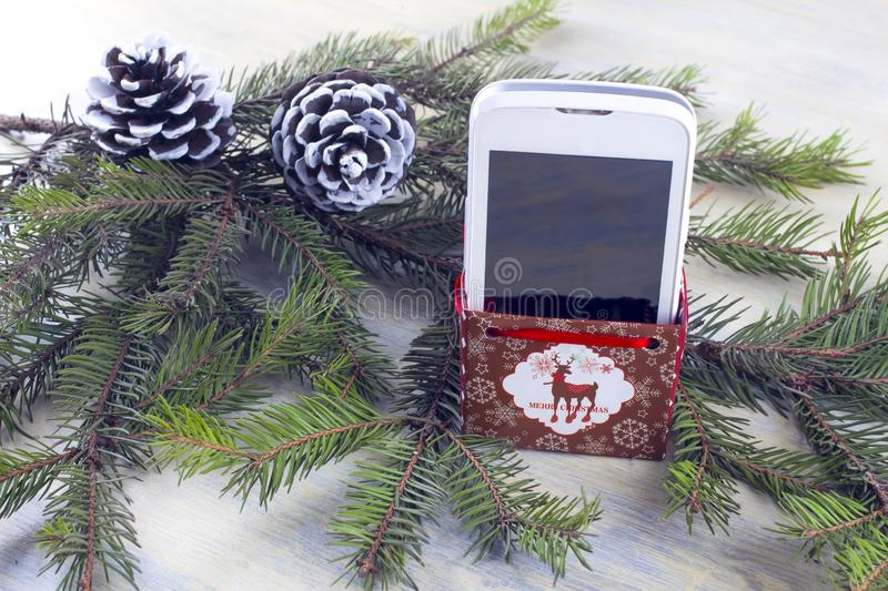 Smartphone in a gift box against the background of Christmas composition royalty free stock photography