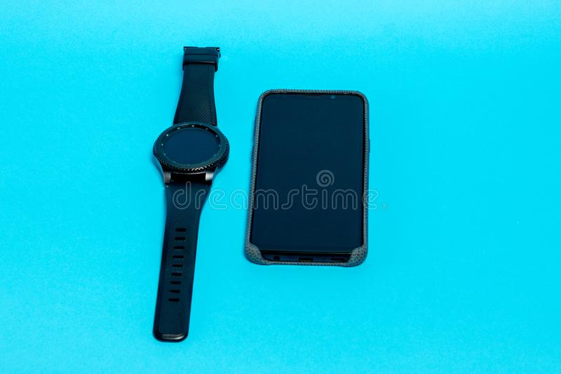Smartphone in a gray textile case and a smart watch on a blue background. Top view. Smartphone in a gray textile case and a smart watch on a blue background royalty free stock photos