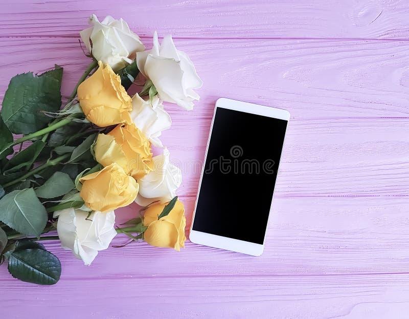 Smartphone gula rosor semestrar den närvarande hälsningtabellen för romans på en rosa träbakgrund royaltyfri fotografi