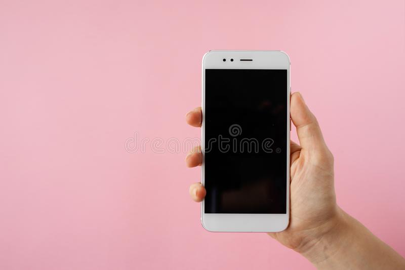 Smartphone in hand, blank screen mock up on pink background. stock images