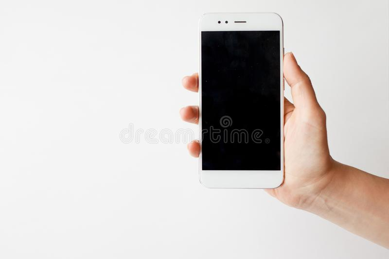Smartphone in hand, blank screen mock up on white background royalty free stock image