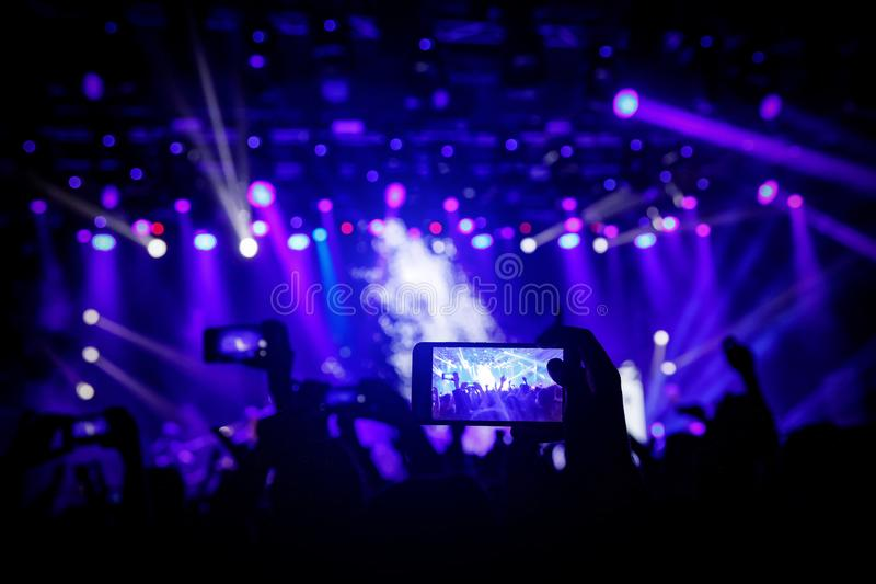 Smartphone in hand at a concert, blue light from stage.  royalty free stock photos