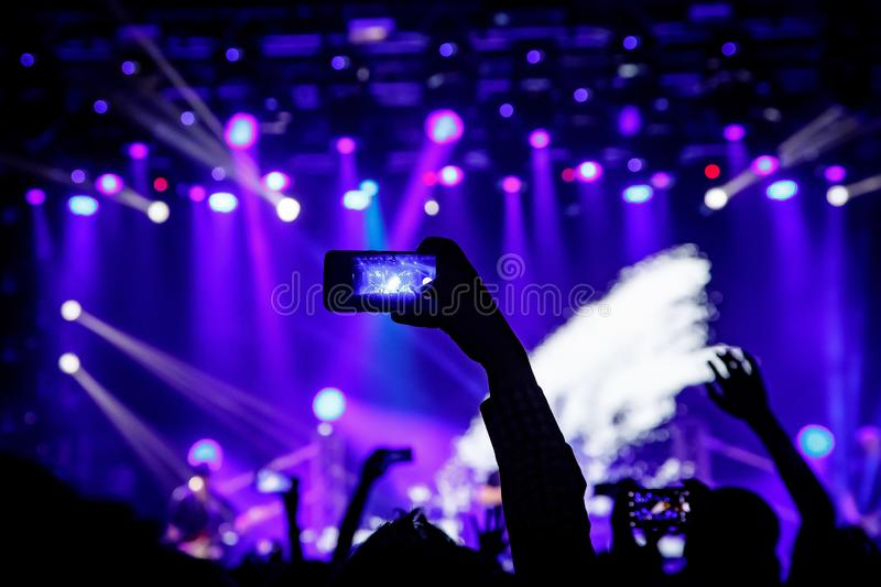 Smartphone in hand at a concert, blue light from stage.  stock images