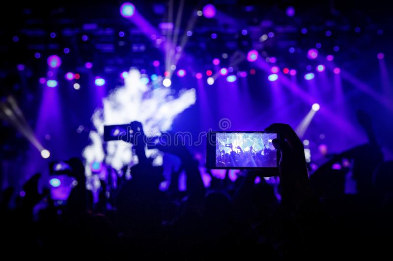 Smartphone in hand at a concert, blue light from stage.  royalty free stock image