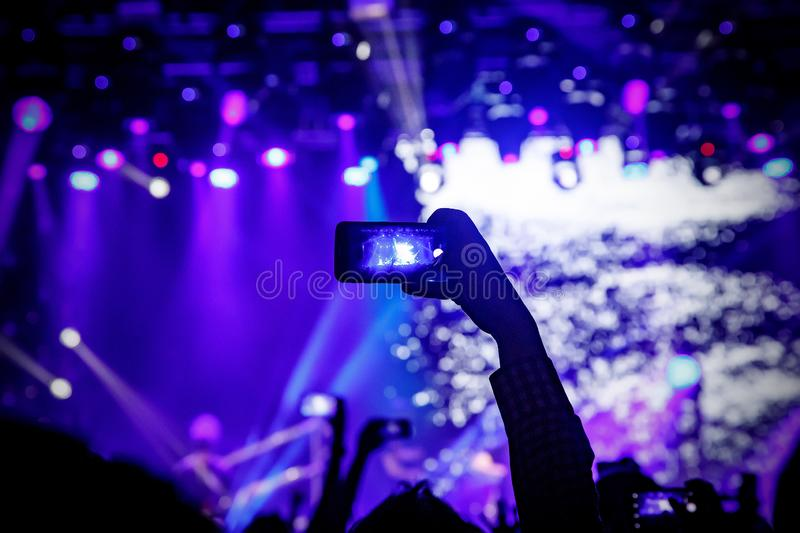 Smartphone in hand at a concert, blue light from stage.  stock image