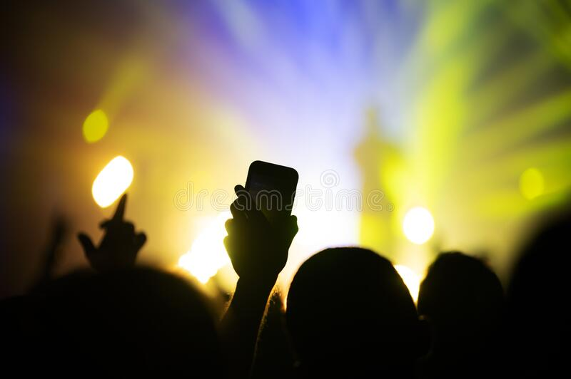 Smartphone in the hand of a fan shooting video and photo for memory at a concert of a favorite artist. The atmosphere of a music f. Estival with a lit stage royalty free stock images