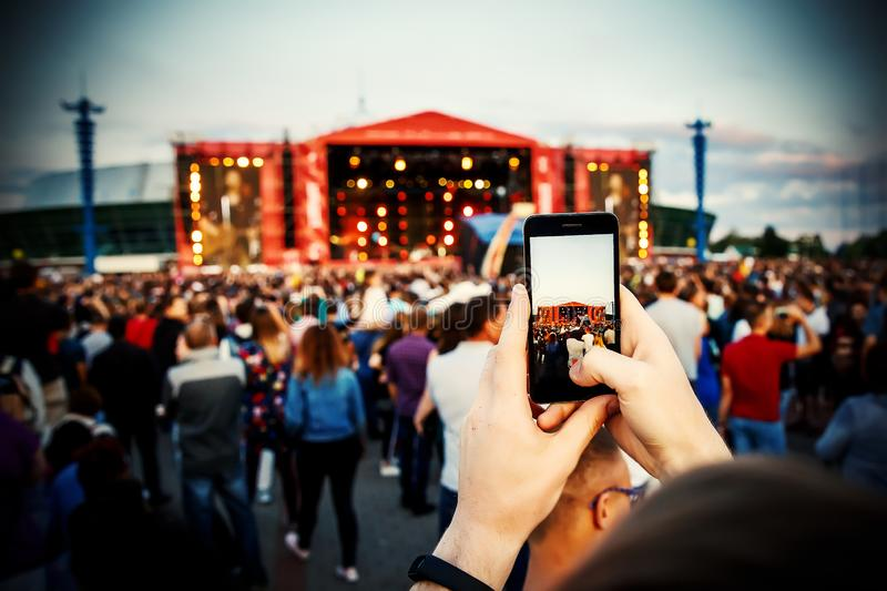 Smartphone in hand. Photographing at the summer music festival.  stock photography