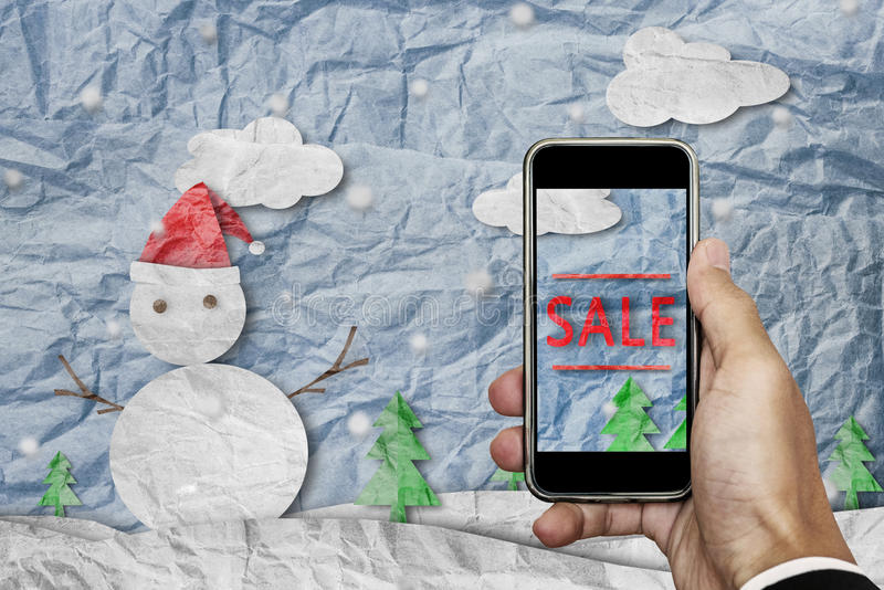 Smartphone on hand with `SALE` on screen, with crumpled paper cut snowman in winter, Christmas shopping sale. Smartphone on hand with `SALE` on screen, with royalty free stock photos