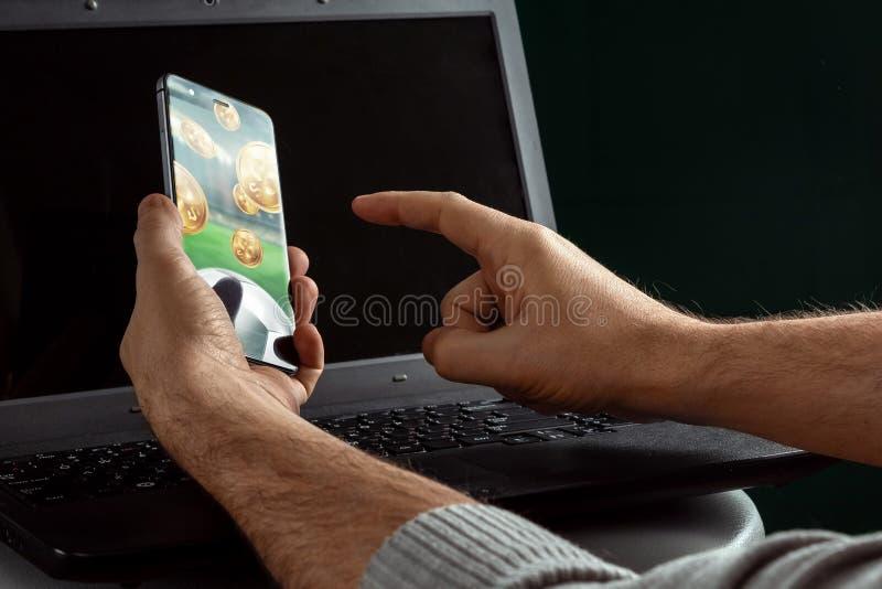 Smartphone in hand Sports Betting op laptop achtergrond Gezelschapsverlof, sportweddenschappen, bookmaker Gemengde media royalty-vrije stock fotografie