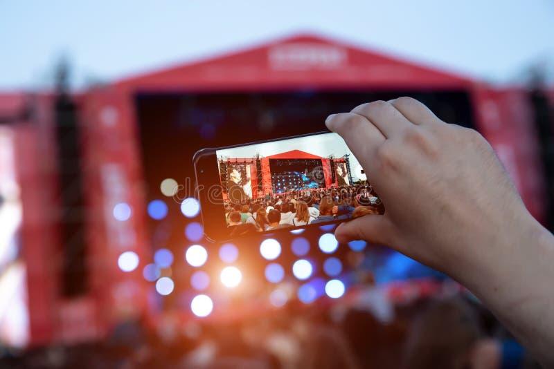 Smartphone in hands during outdoor rock concert royalty free stock photo