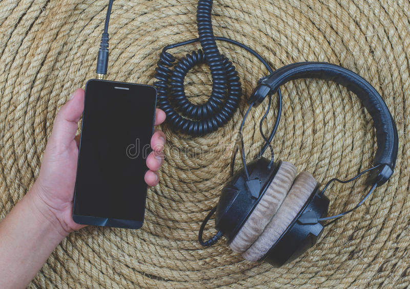 Smartphone headphone music on a jute rope background. Smartphone and headphone music on a jute rope background royalty free stock photography