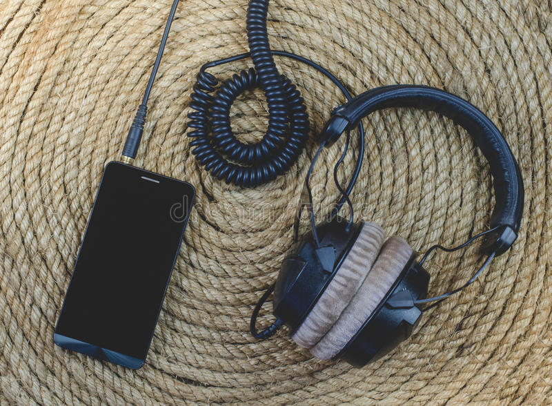 Smartphone and headphone music on a rope background. Smartphone and headphone music on a jute rope background royalty free stock photos