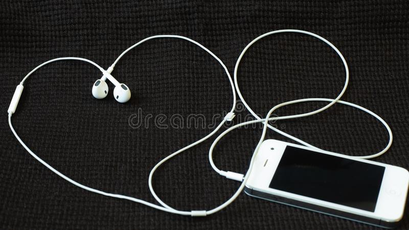 Smartphone with headphones that lie like a heart on a dark textured fabric royalty free stock photo