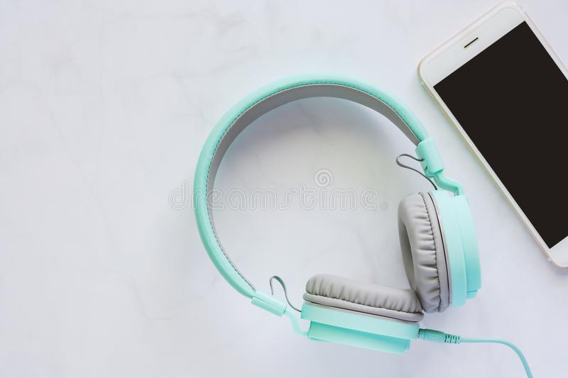 Smartphone with headphones on white marble background royalty free stock photography