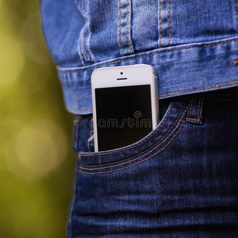 Smartphone in het dagelijkse leven Telefoon in jeanszak stock afbeelding