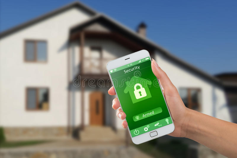 Smartphone with home security app in a hand on the building background. Smartphone with home security app in hand on the building background royalty free stock photo