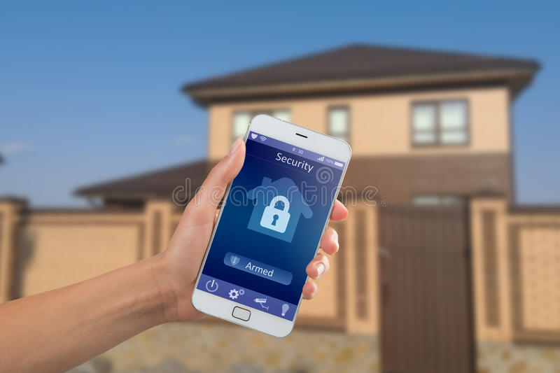 Smartphone with home security app in a hand on the building background stock photography