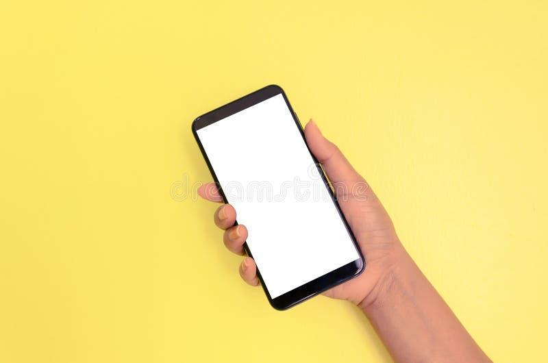 Smartphone humano de la tenencia de la mano con el fondo de pantalla blanco imagen de archivo