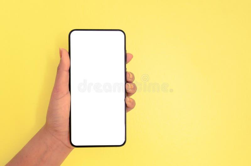 Smartphone humano de la tenencia de la mano con el fondo de pantalla blanco imagenes de archivo