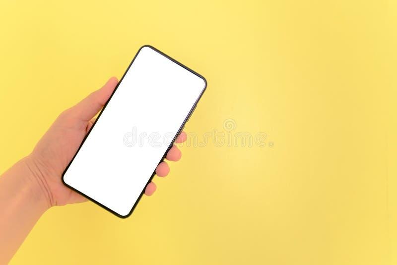 Smartphone humano de la tenencia de la mano con el fondo de pantalla blanco imágenes de archivo libres de regalías