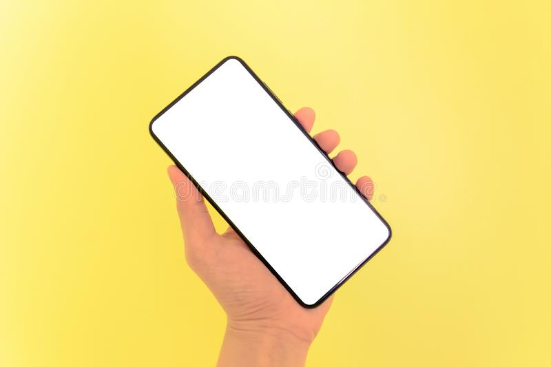 Smartphone humano de la tenencia de la mano con el fondo de pantalla blanco foto de archivo libre de regalías