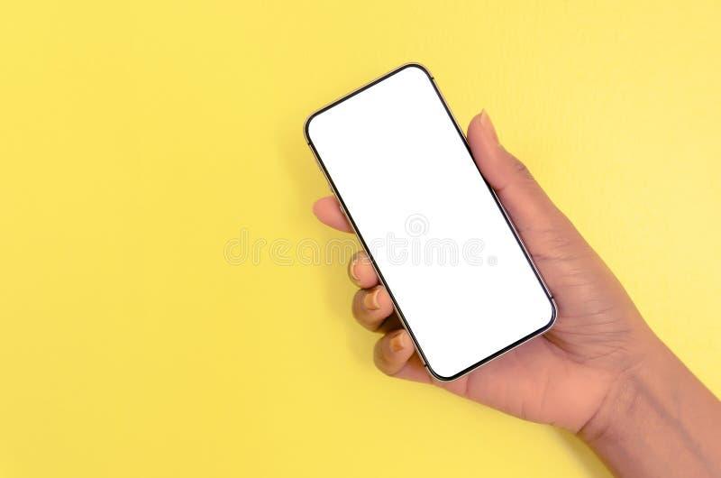 Smartphone humano de la tenencia de la mano con el fondo de pantalla blanco fotografía de archivo libre de regalías