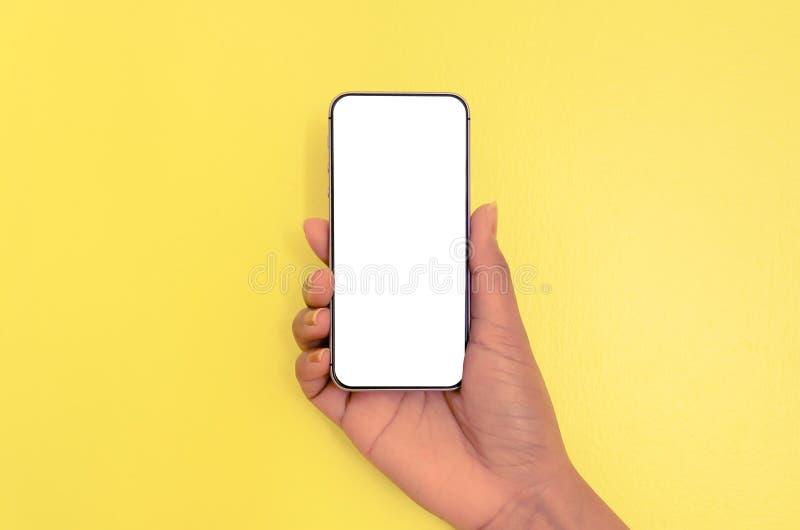 Smartphone humano de la tenencia de la mano con el fondo de pantalla blanco imagen de archivo libre de regalías