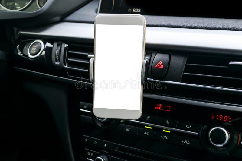 Smartphone i ett bilbruk för Navigate eller GPS Körning av en bil med Smartphone i hållare Mobiltelefon med den isolerade vita sk arkivfoton