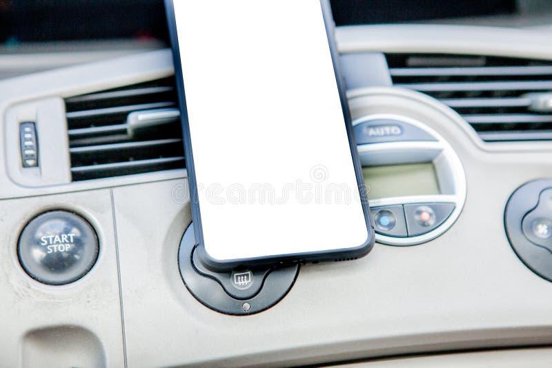 Smartphone i ett bilbruk för Navigate eller GPS Körning av en bil med Smartphone i hållare Vit skärm för mobiltelefon _ royaltyfria bilder