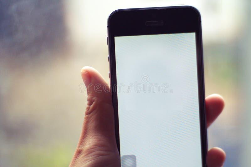 Smartphone i hand - folk och teknologibegrepp royaltyfria bilder
