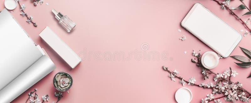 Smartphone i otwarty magazyn wyśmiewamy w górę pastelowych menchii desktop tła z kosmetykami na i okwitnięcie rozgałęzia się, odg obraz royalty free