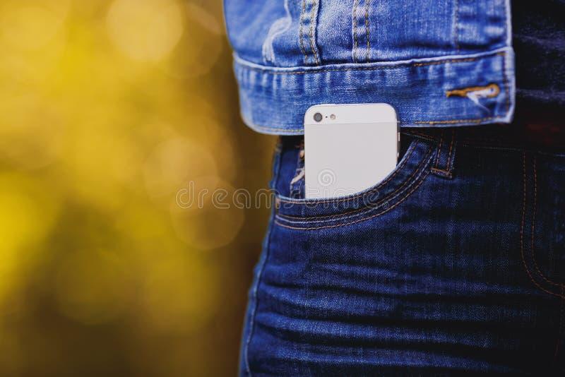 Smartphone i vardagsliv Telefon i jeansfack arkivbilder