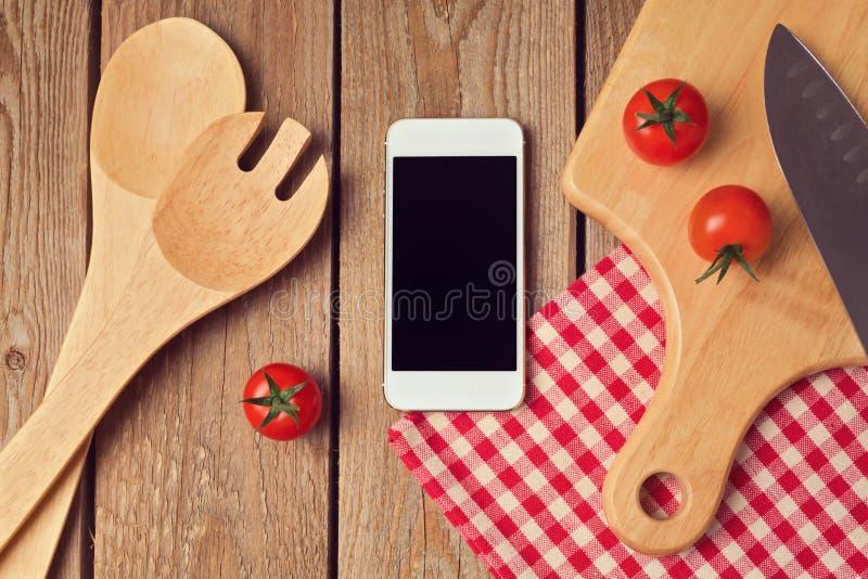 Smartphone imita encima de la plantilla para cocinar la exhibición de los apps imagen de archivo