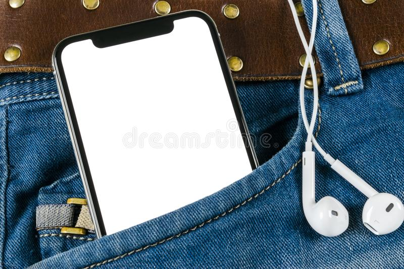Smartphone with isolated white screen in jeans pocket with earphones. Business workplace with copy space. Empty space for text. Isolated screen for mock up stock photos