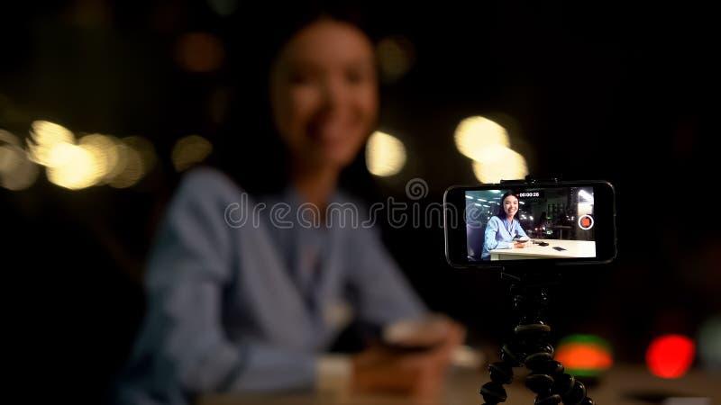 Smartphone-Kamerastativ, der weibliche Bloggersitzentabelle, on-line-Gesch?ft notiert stockfoto