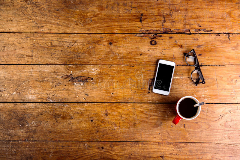 Smartphone, kopp kaffe och glasögon på kontorsskrivbordet arkivbilder