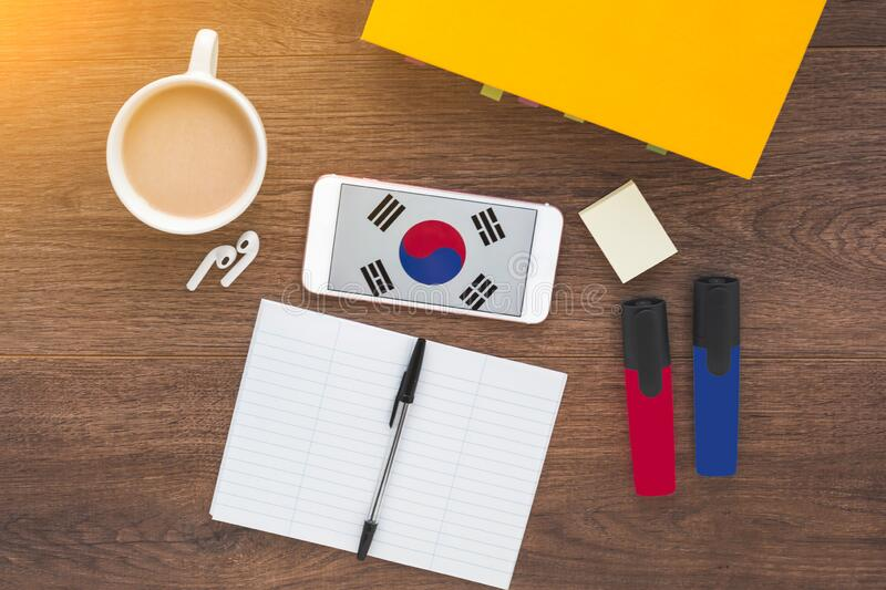 Smartphone with Korean flag on a wooden dark background, textbook, wireless headphones. Language learning concept stock photography