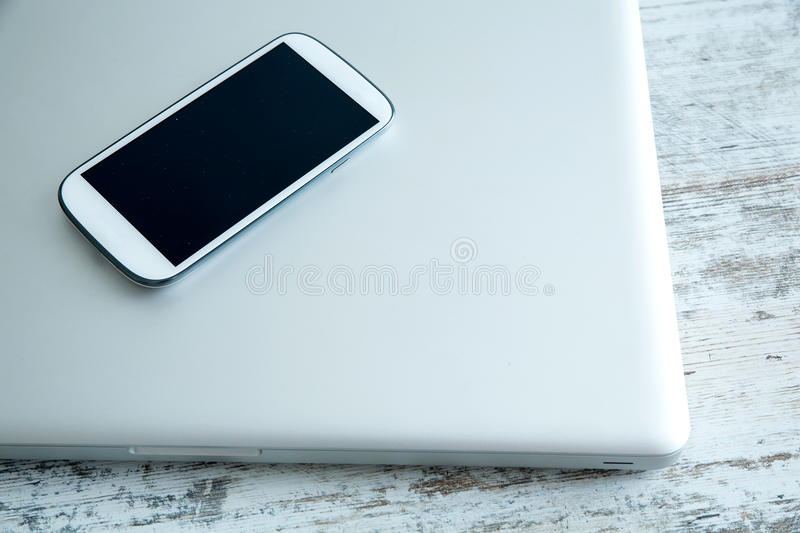 Smartphone and a laptop computer royalty free stock photos