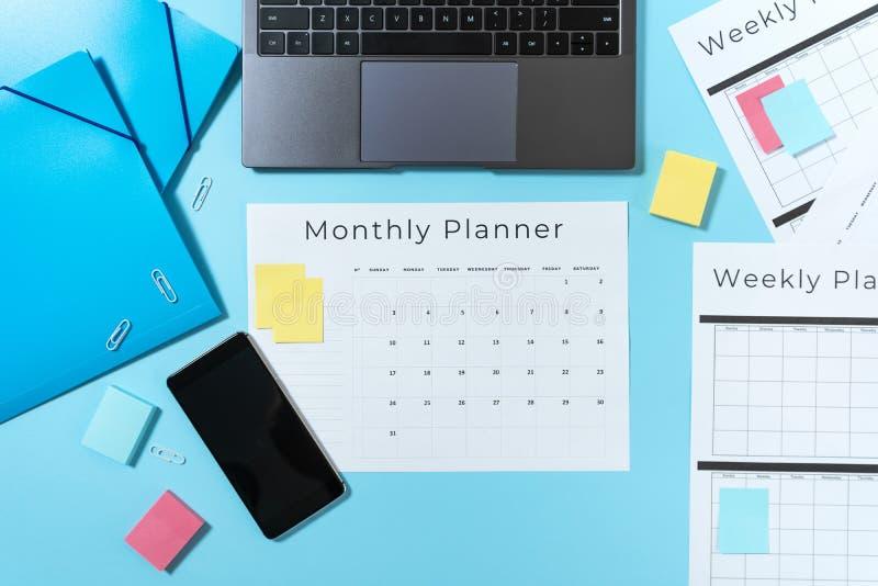 Smartphone, laptop, kantoorbehoeften en ontwerper op blauwe pastelkleurachtergrond royalty-vrije stock afbeeldingen