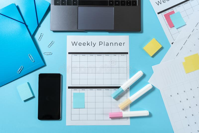 Smartphone, laptop, kantoorbehoeften en ontwerper op blauwe pastelkleurachtergrond stock afbeelding