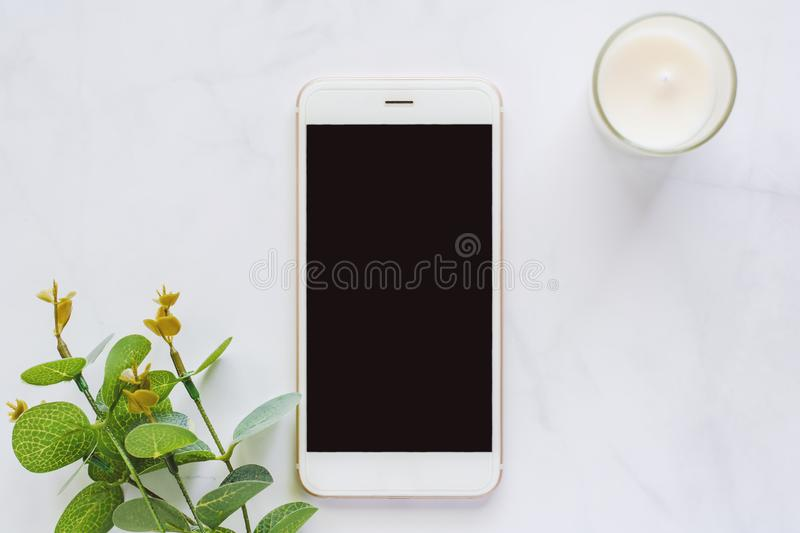 Smartphone with leaf bouquet and aromatic candle on white marble stock photos