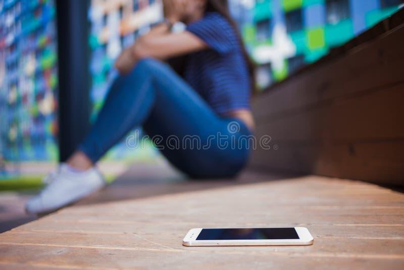 Smartphone lying on the beach w pierwszoplanowym, zamazanym tle, dziewczyna, płacz, zakrywa twarz podczas gdy siedzący na drewnia fotografia stock