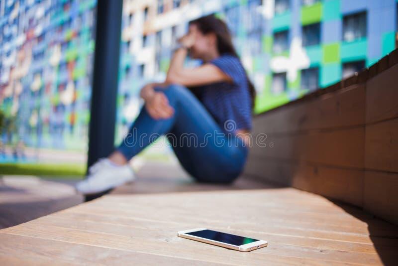 Smartphone lying on the beach w pierwszoplanowym, zamazanym tle, dziewczyna, płacz, zakrywa twarz podczas gdy siedzący na drewnia zdjęcia royalty free