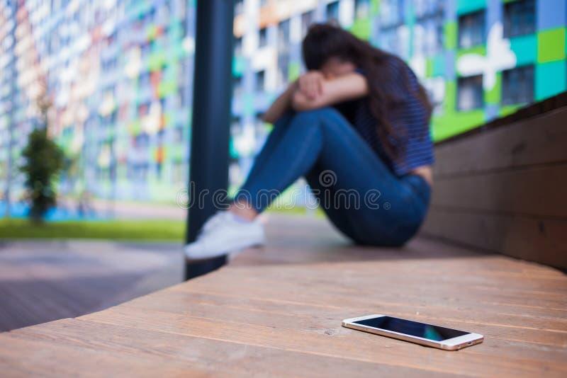 Smartphone lying on the beach w przedpolu na zamazanym tle, dziewczyna, chujący twarz w jej kolanach, siedzi na drewnianej ławce zdjęcia royalty free