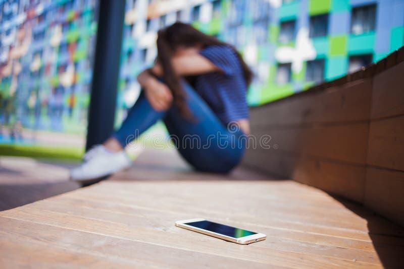 Smartphone lying on the beach w przedpolu na zamazanym tle, dziewczyna, chujący twarz w jej kolanach, siedzi na drewnianej ławce zdjęcie stock
